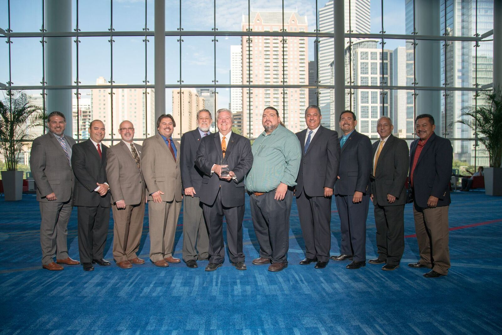 11 Harlingen employees together with one holding award at event